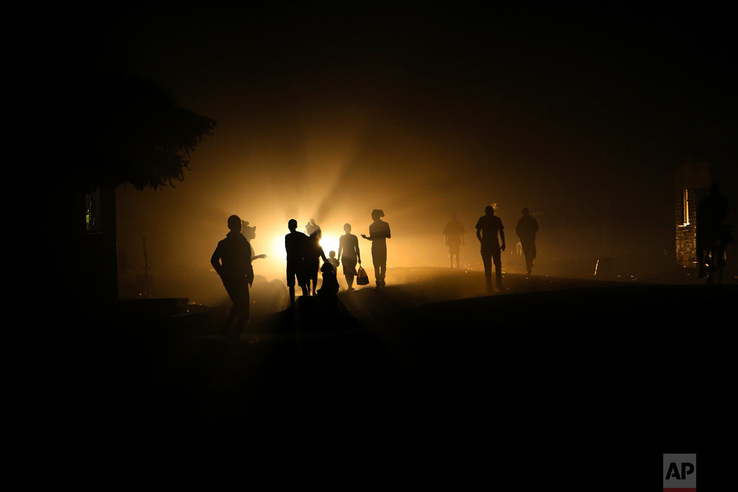People walk home in the dark due to power shortages in Harare, on Monday Sept. 30, 2019. Zimbabwe's opposition lawmakers walked out of Parliament on Tuesday as President Emmerson Mnangagwa presented his state of the nation address, a sign of the political tensions still gripping the country. (AP Photo/Tsvangirayi Mukwazhi)