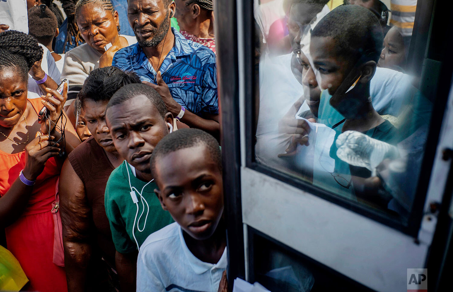 Haitian migrants displaced from their homes destroyed by Hurricane Dorian at Abaco Island wait to get on a bus to receive aid from humanitarian organizations, in Nassau, Bahamas, Sunday, Sept. 29, 2019. A preliminary report estimates Dorian caused some $7 billion in damage, but the government has not yet offered any figures. (AP Photo/Ramon Espinosa)