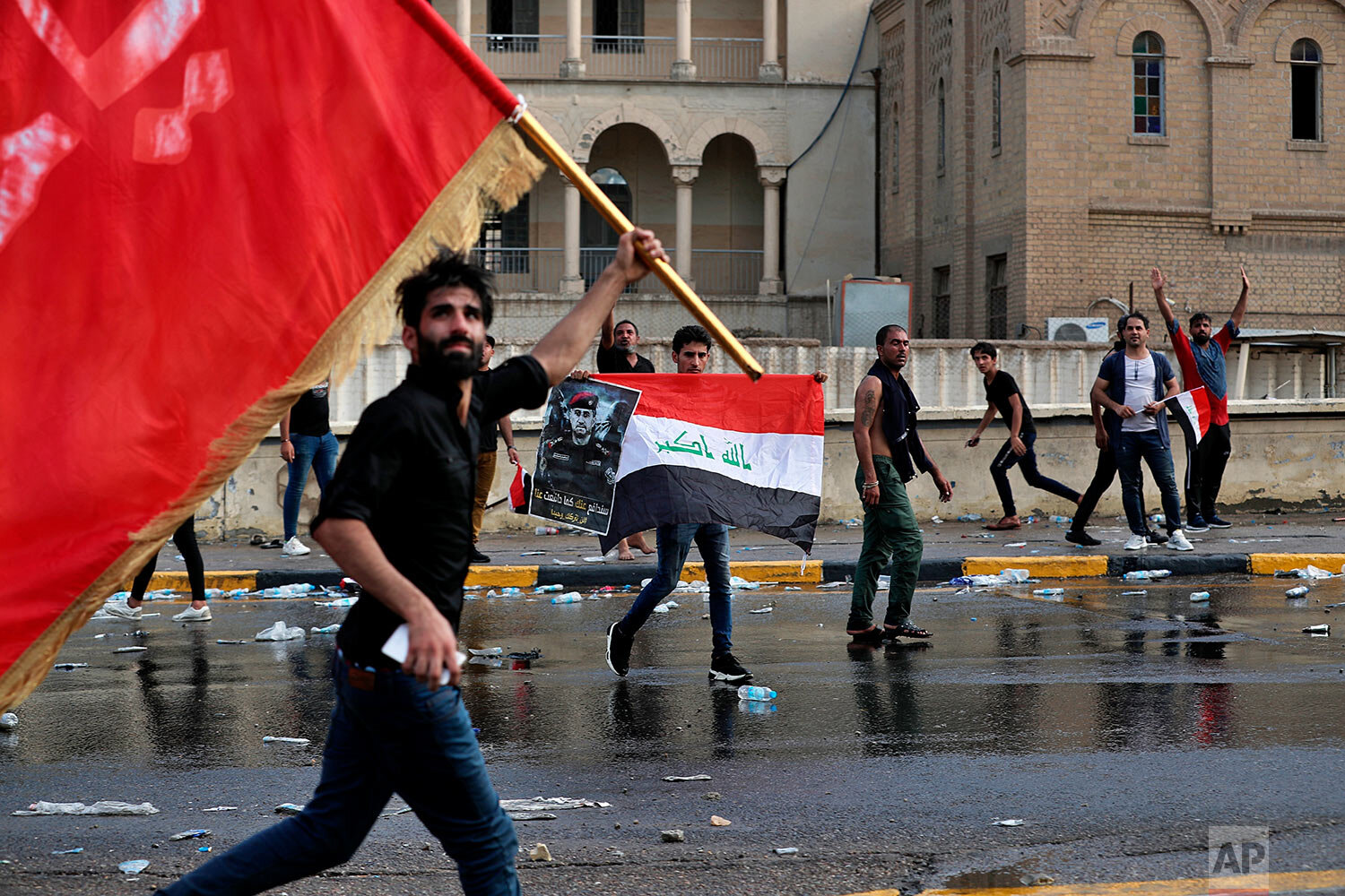 Protestors wave flags and hold a poster of Lt. Gen. Abdul-Wahab al-Saadi during a protest in Tahrir Square, in central Baghdad, Iraq, Tuesday, Oct. 1, 2019. Spontaneous rallies, which began Tuesday, started as mostly young demonstrators took to the streets demanding jobs, improved services like electricity and water, and an end to corruption in the oil-rich country. In a desperate attempt to curb massive rallies, authorities blocked the internet and imposed an around-the-clock curfew in the capital. (AP Photo/Khalid Mohammed)