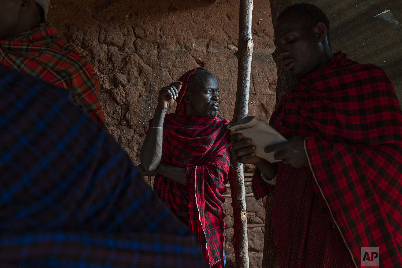 Maasai tribesmen meet in the village of Loibor Siret, Tanzania, Friday July 5, 2019. (AP Photo/Jerome Delay)