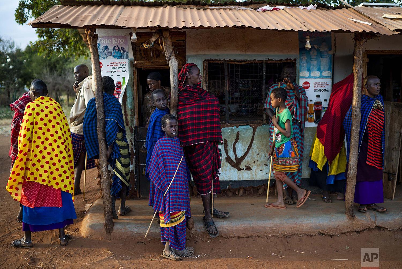 Maasai tribesmen hang out in the village of Loibor Siret, Tanzania, Friday, July 5, 2019. (AP Photo/Jerome Delay)