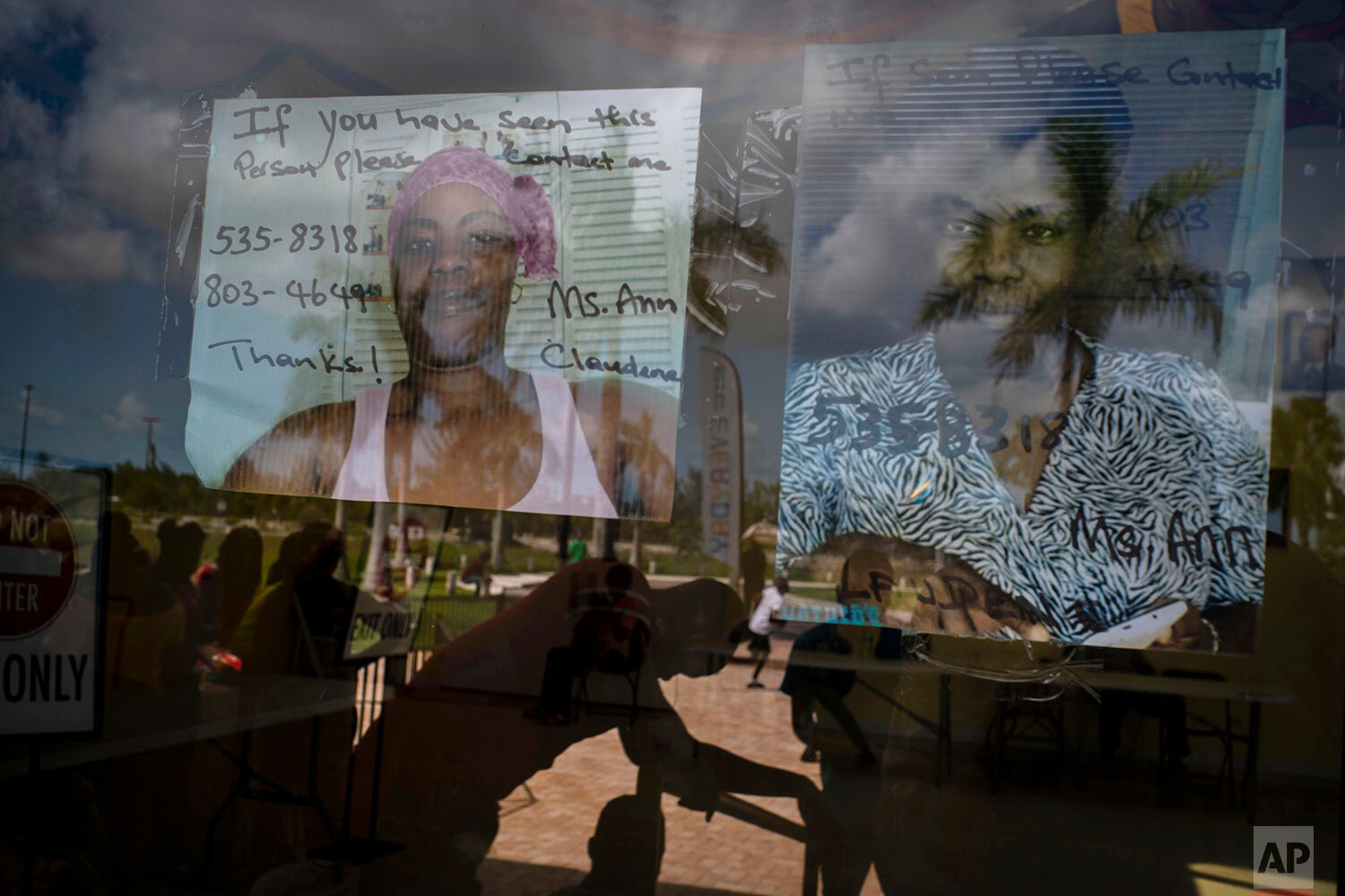 Photos of two women missing during Hurricane Dorian hang from the door of the shelter for displaced people from Abaco because of the destruction by Hurricane Dorian in Nassau, Bahamas, Saturday, Sept. 28, 2019.  (AP Photo / Ramon Espinosa)