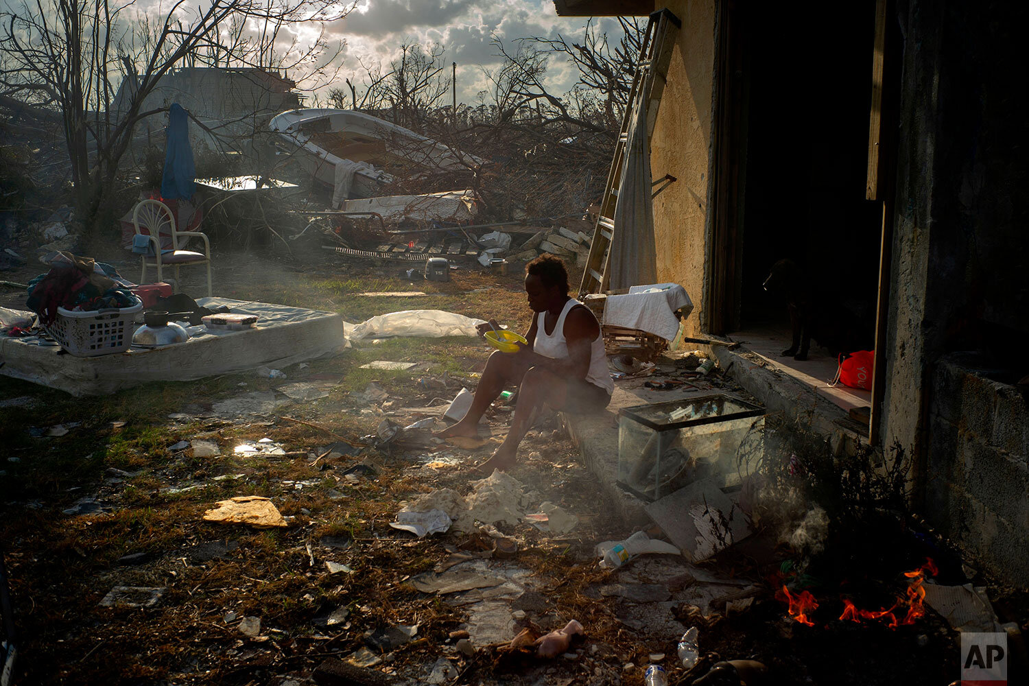 Tereha Davis, 45, eats a meal of rice as she sits among the remains of her shattered home, in the aftermath of Hurricane Dorian in McLean's Town, Grand Bahama, Bahamas, Wednesday Sept. 11, 2019.  (AP Photo/Ramon Espinosa)