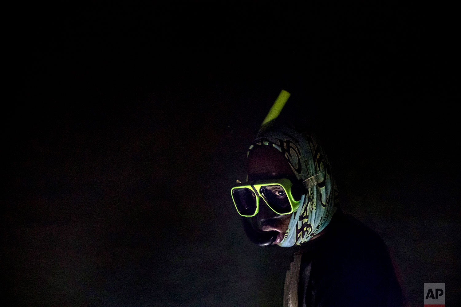 Nicholas Bingham enters the water to go night spearfishing, which is banned, especially in the sanctuaries set up to protect the island's endangered coral reefs and replenish fish stocks, in Stewart Town, Jamaica, Friday, Feb. 15, 2019. The restrictions have taken a toll on many Jamaicans' livelihoods, in a place where jobs can be scarce. In some places, fishermen have joined with local businesses to form marine associations and negotiate a no-fishing zone. But that simple line in the water must be enforced. (AP Photo/David Goldman)
