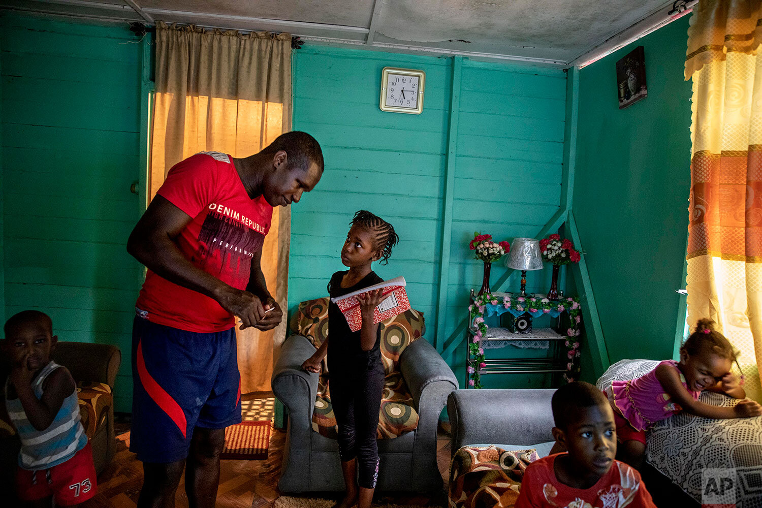 """Fisherman Damian Brown helps his daughter Mishaunda, 9, with her homework as his sons Damian Jr., 3, from left, Dre, 4, and daughter Paris, 1, right, watch television in their home in Stewart Town, Jamaica, Thursday, Feb. 14, 2019. Brown has been caught twice fishing inside a no-take zone and now relies more on night spearfishing, which is illegal, to make up for the wages impacted by the sanctuary's restrictions. """"Was nice before the sanctuary come in. Was good,"""" said Brown. """"Now I make no money off the sea again like one time."""" (AP Photo/David Goldman)"""