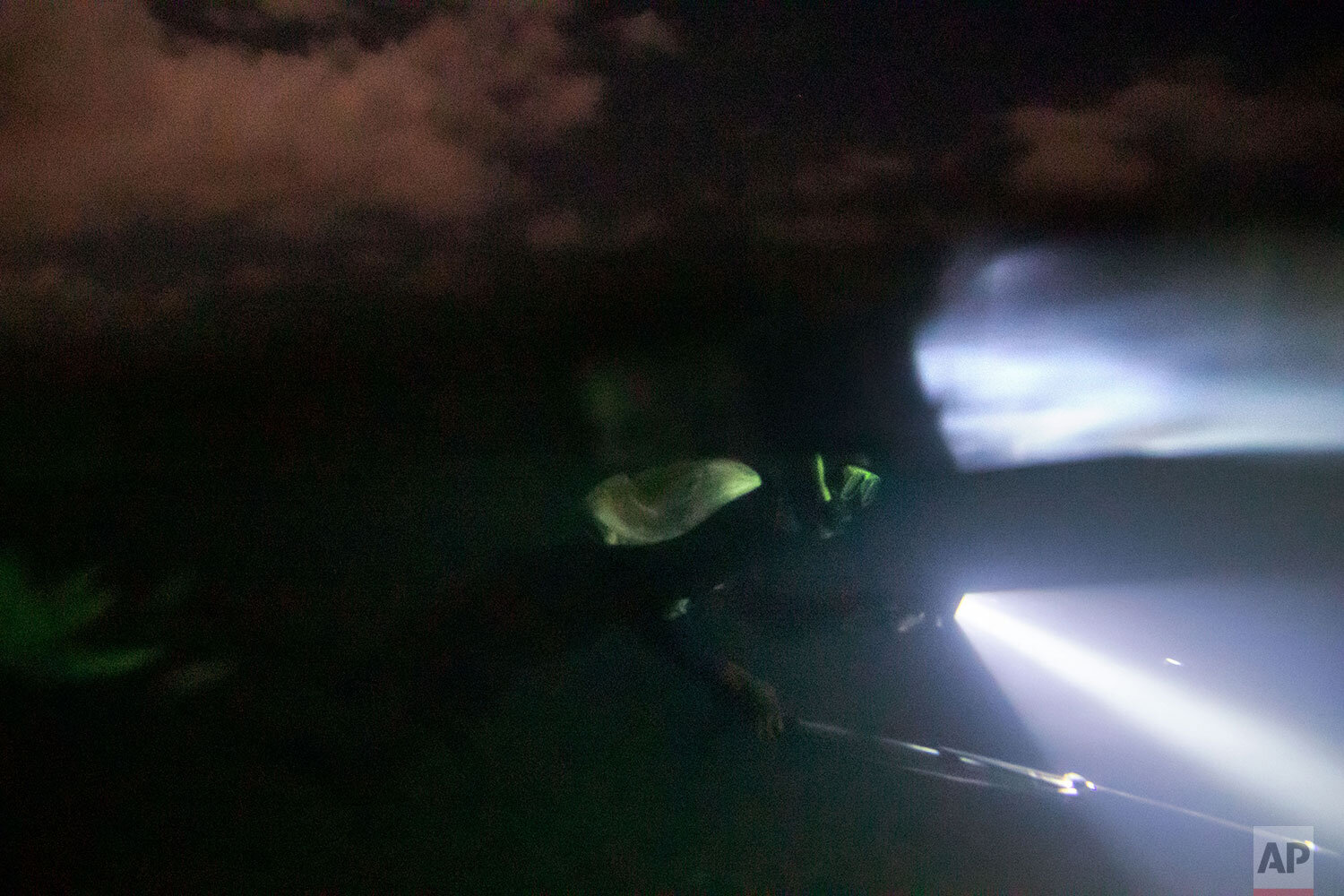 Nicholas Bingham spearfishes at night, which is banned, under a moonlit sky, in Stewart Town, Jamaica, Friday, Feb. 15, 2019. Night spearfishermen wrap their faces to protect against stinging jellyfish. But that's not the only threat lurking in the water: In addition to sharks, wardens are patrolling, scouting for illegal fishing. (AP Photo/David Goldman)