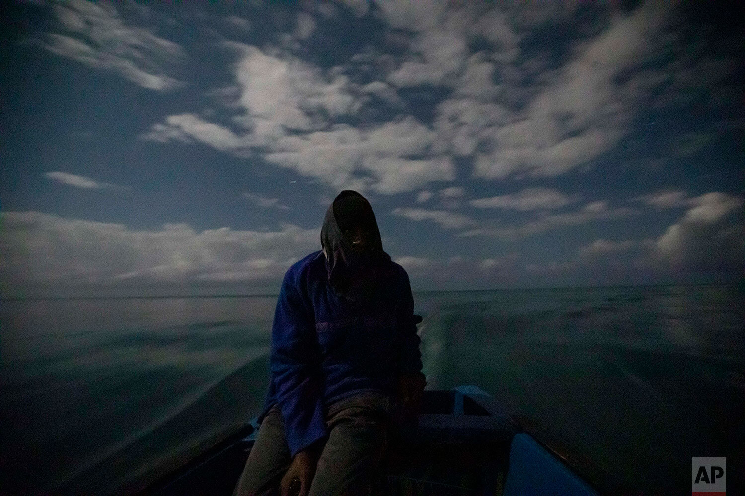 White River Fish Sanctuary warden Mark Lobban steers the boat under moonlight while patrolling the no-take zone for illegal fishermen in Ocho Rios, Jamaica, Friday, Feb. 15, 2019. Two years ago, fishermen joined with local businesses to form a marine association and negotiate the boundaries for a no-fishing zone stretching two miles along the coast. A simple line in the water is hardly a deterrent, however, for a boundary to be meaningful, it must be enforced. (AP Photo/David Goldman)