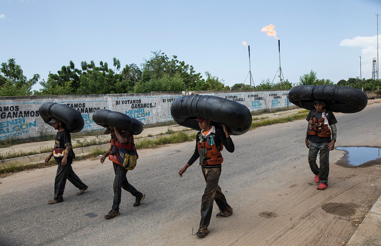 Oil-covered fishermen carry home the truck tire inner tubes they use to float on and fish from on Lake Maracaibo in Cabimas, Venezuela, July 12, 2019. (AP Photo/Rodrigo Abd)