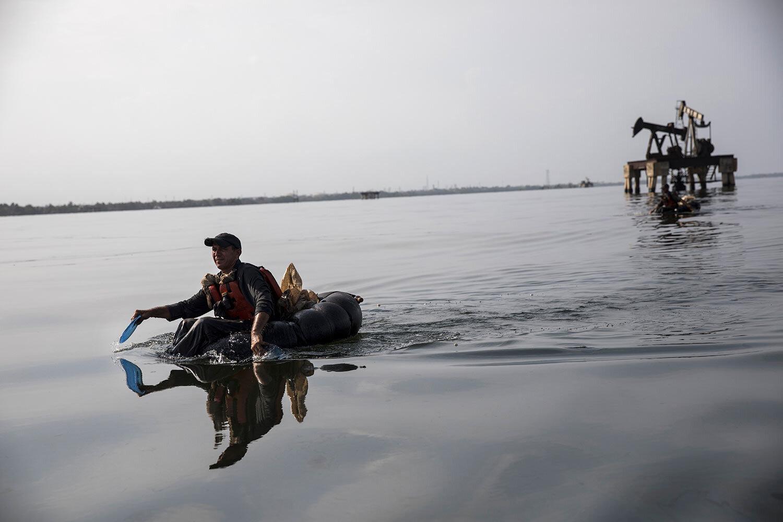 "A fisherman known as a ""tripero"" paddles from the inner tube of a truck tire on Lake Maracaibo, near La Salina crude oil shipping terminal near Cabimas, Venezuela, May 22, 2019. (AP Photo/Rodrigo Abd)"