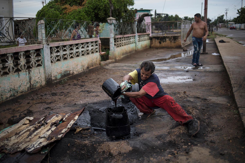 Jose Lugano collects crude oil leaking near the pipes that carry gas to his kitchen, near Lake Maracaibo, in Cabimas, Venezuela, May 24, 2019. (AP Photo/Rodrigo Abd)