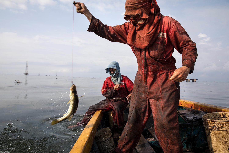 "Fishermen wearing oil stained uniforms from Venezuela's state-run oil firm PDVSA, catch bass known as ""robalo"" near La Salina crude oil shipping terminal, on Lake Maracaibo near Cabimas, Venezuela, May 18, 2019. (AP Photo/Rodrigo Abd)"