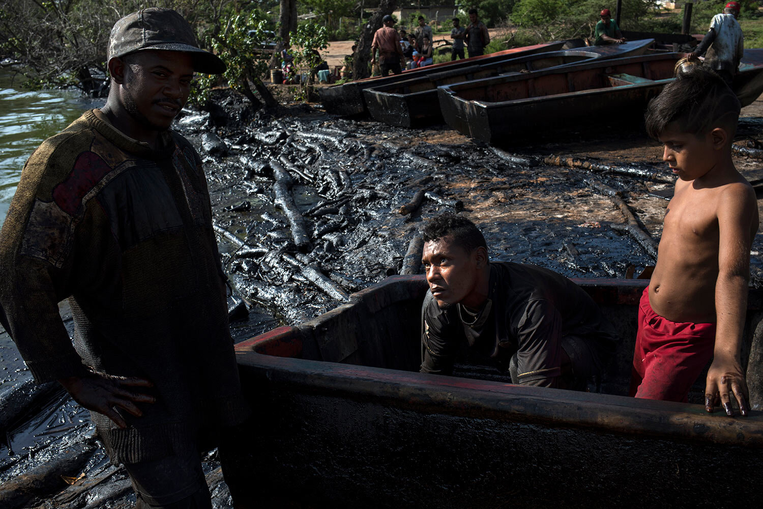 Fishermen Erick Alejandro, left, and Kelvin Alcala remove oil accumulated inside their boat after a workday on the oil-soaked shore of Lake Maracaibo in Cabimas, Venezuela, July 4, 2019. (AP Photo/Rodrigo Abd)