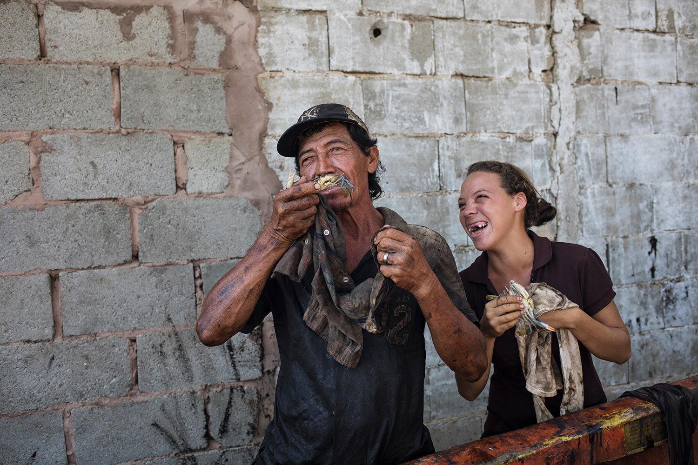 Fisherman Antonio Tello jokes around with his daughter Genesis Tello as they clean the oil covered crabs he just caught in Lake Maracaibo in Punta Gorda, Cabimas, Venezuela, July 11, 2019. (AP Photo/Rodrigo Abd)