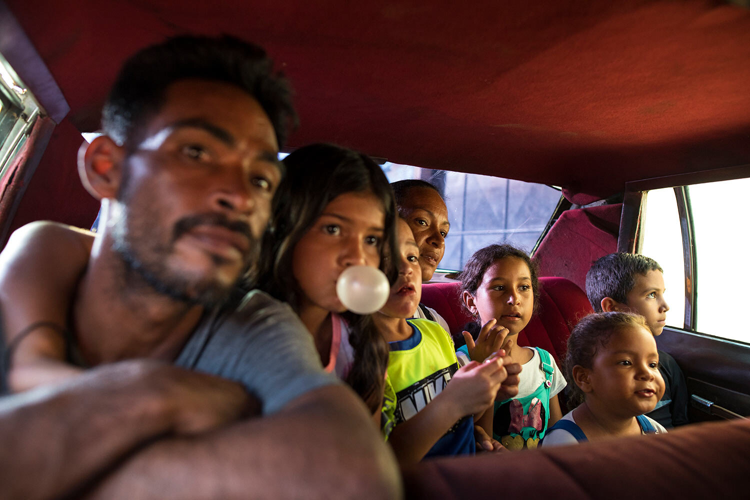 In this July 3, 2019 photo, members of the Rodriguez family travel in a 1970's car while going to buy food in Cabimas, Venezuela. (AP Photo/Rodrigo Abd)
