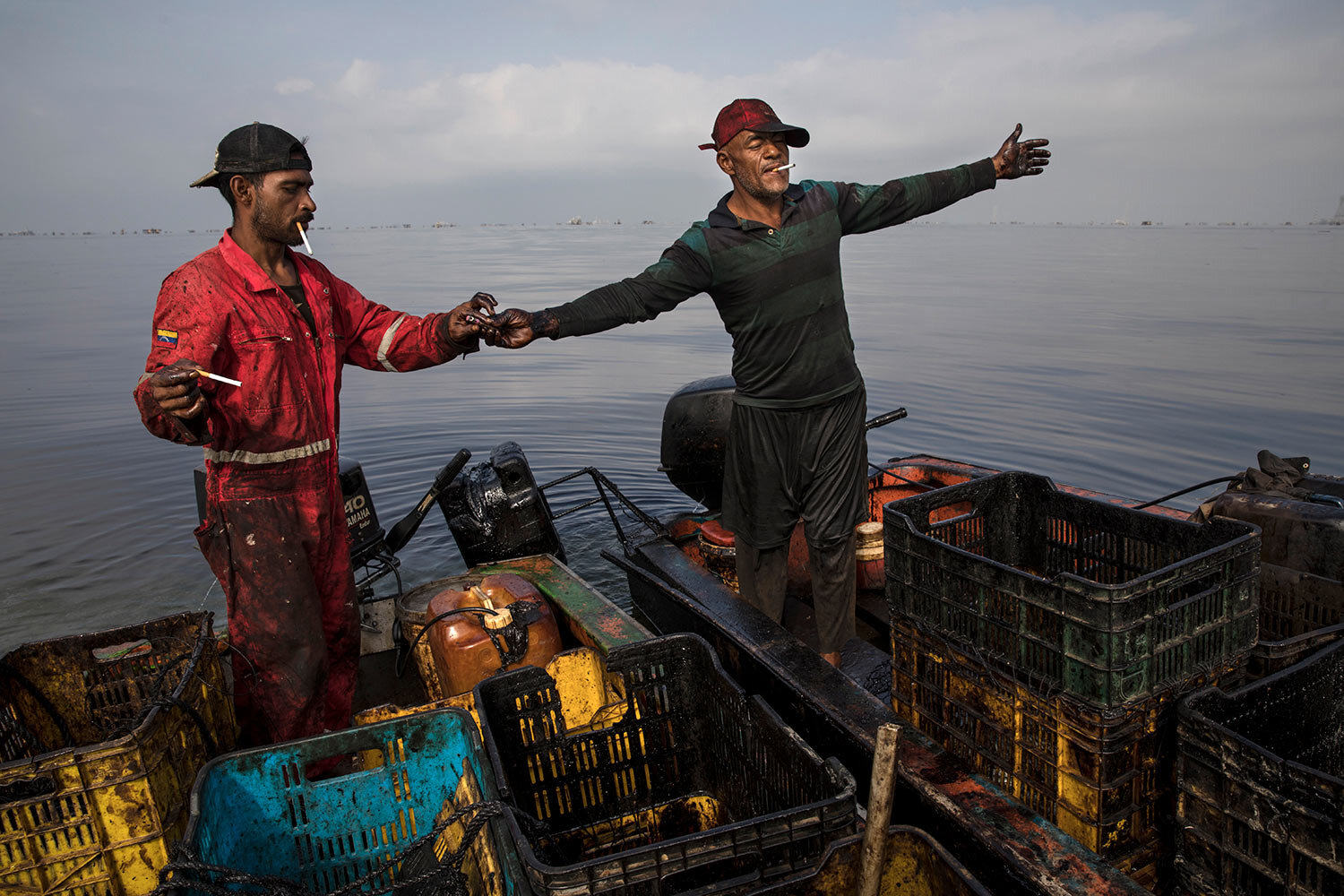 Crab fisherman whose clothing and equipment are soaked with oil take a smoke break on Lake Maracaibo near Punta Gorda, Cabimas, Venezuela, May 17, 2019. An explosion badly burned three fishermen recently when they fired up their boat's motor near a natural gas leak that bubbles up from the bottom of the lake, engulfing them in flames. (AP Photo/Rodrigo Abd)