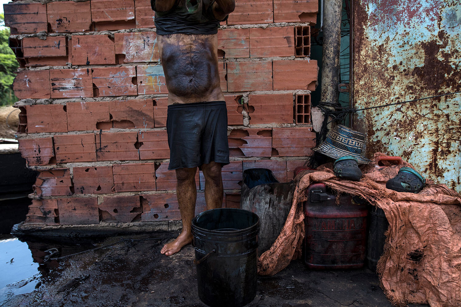 Fisherman Manuel Nune's stomach is covered in oil, as he cleans up after a day of crab fishing on Lake Maracaibo in Cabimas, Venezuela, July 4, 2019. Fishermen wash the oil from their bodies with raw gasoline. They say the prickly rash in their skin is the price of survival. (AP Photo/Rodrigo Abd)