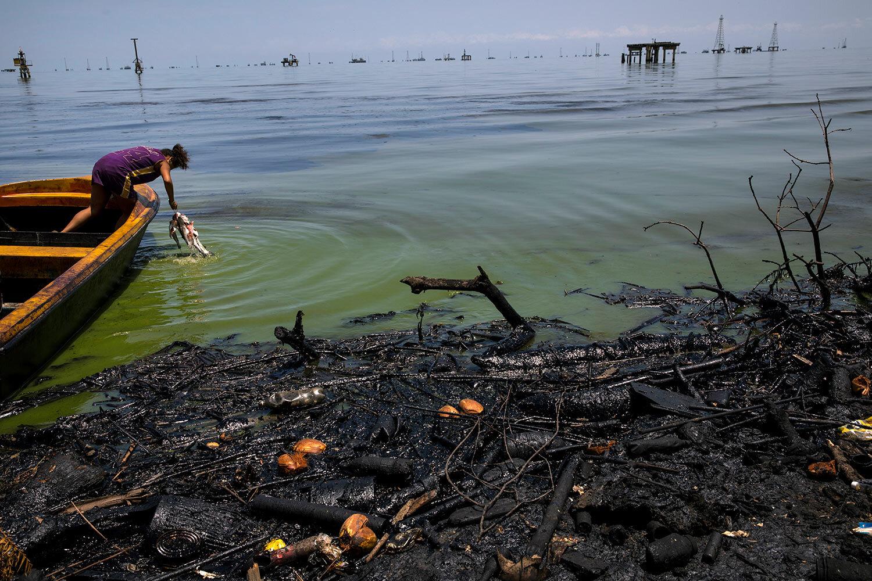 Fabiola Elizalzabal washes fish caught by her father near La Salina crude oil shipping terminal on Lake Maracaibo, next to an oil-covered shore in Cabimas, Venezuela, July 3, 2019. (AP Photo/Rodrigo Abd)