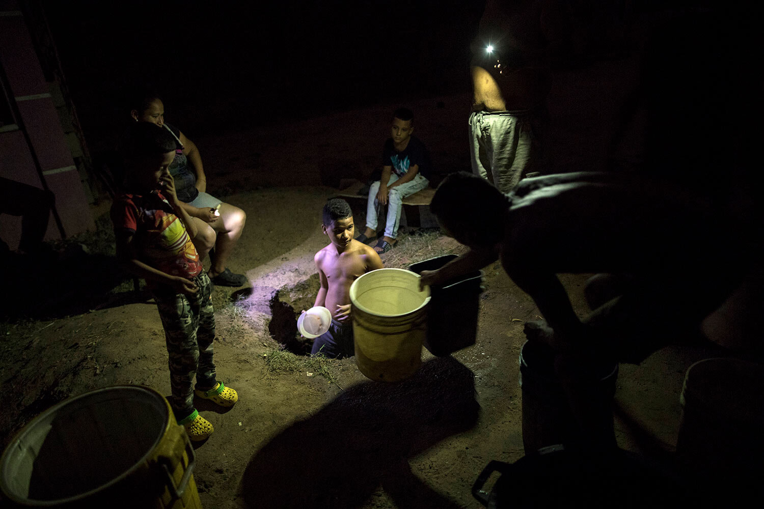 A youth draws water from a well that was created on the roadside by locals looking to resolve the lack of running water and electricity in Cabimas, Venezuela, July 12, 2019. (AP Photo/Rodrigo Abd)