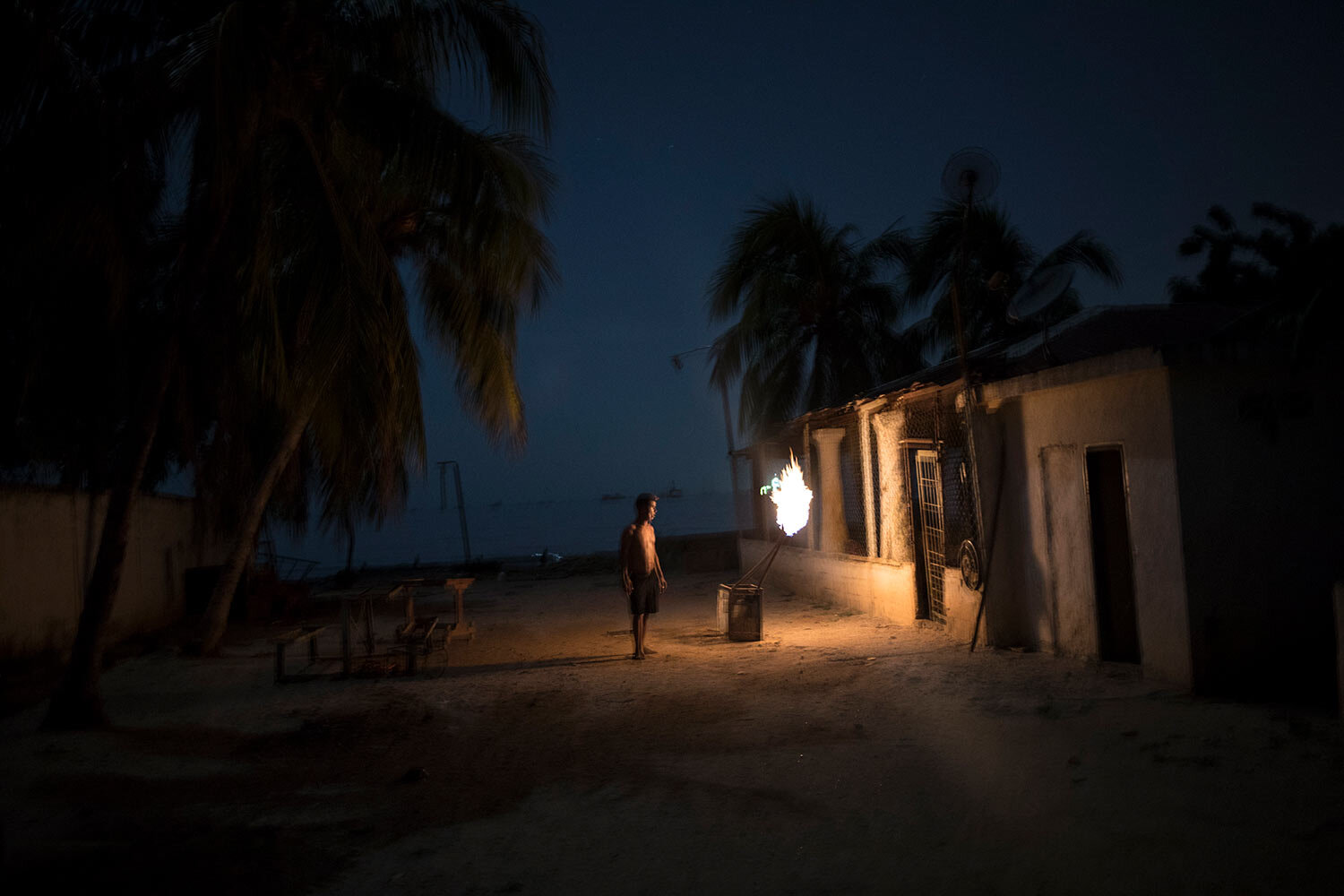 """During a blackout, a man is illuminated by torches made out of crude oil, and known as """"mechurrios,"""" referring to the flares that burn excess gas on oil wells, in Cabimas, Venezuela, July 11, 2019. (AP Photo/Rodrigo Abd)"""
