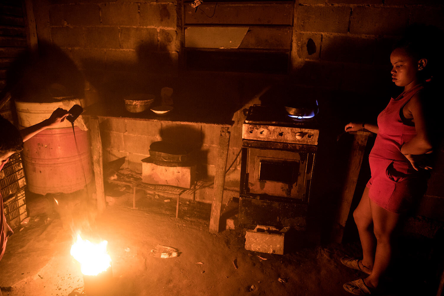 """During a blackout, oil is added to a bucket of fire, known as a """"mechurrio,"""" which is the name for the flares that burn excess gas on top of oil wells, inside a home where Fabiola Elizalzabal cooks dinner in Cabimas, Venezuela, May 16, 2019. (AP Photo/Rodrigo Abd)"""