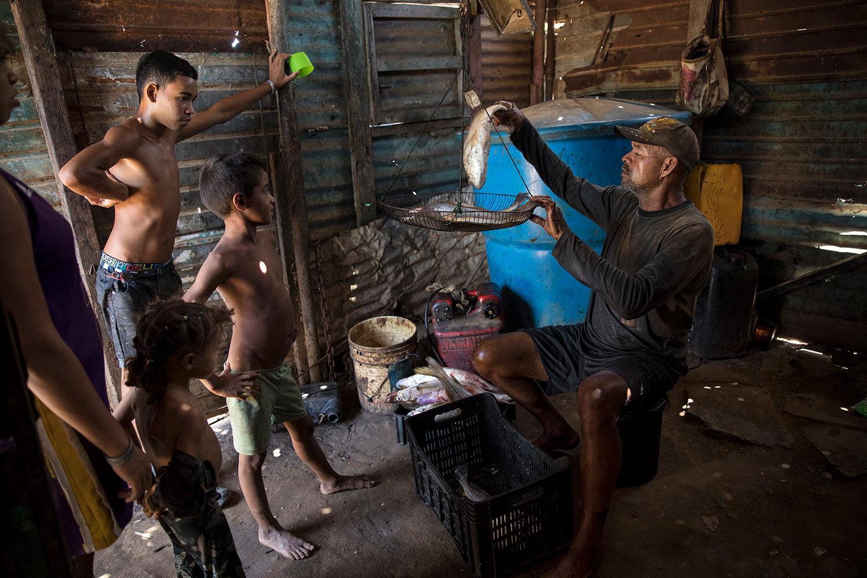 Fisherman Alejandro Elizalzabal weighs his catch after a work day on Lake Maracaibo in Cabimas, Venezuela, July 3, 2019. (AP Photo/Rodrigo Abd)