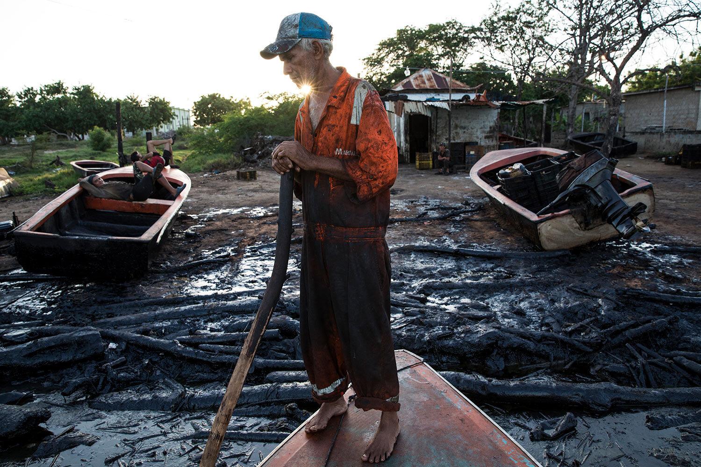 Fisherman William Vilchez arrives to the oil-covered shoreline of Lake Maracaibo in Cabimas, Venezuela, May 18, 2019. (AP Photo/Rodrigo Abd)
