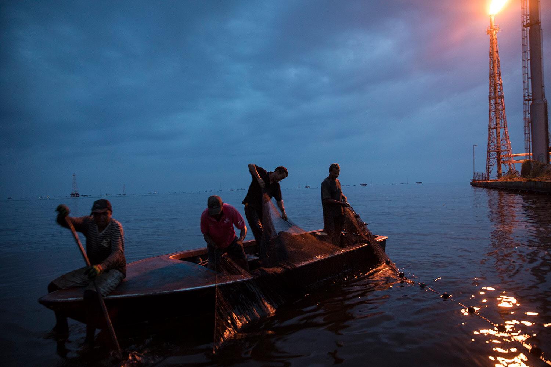 Fishermen pull in their nets as they fish for shrimp near La Salina crude oil shipping terminal, behind, on Lake Maracaibo near Cabimas, Venezuela, at sunset May 22, 2019. (AP Photo/Rodrigo Abd)