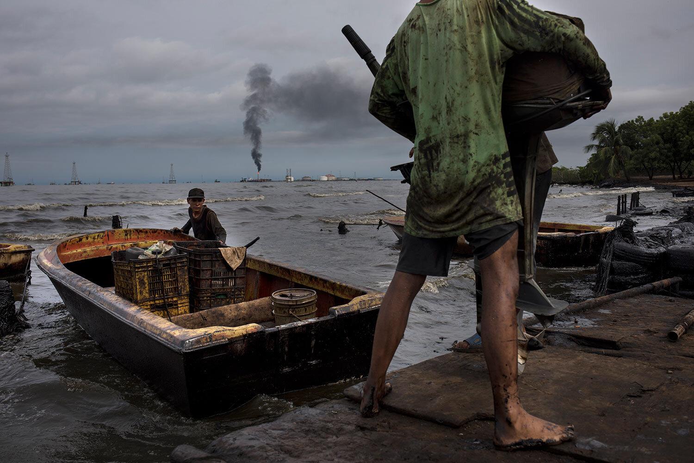 Fishermen covered in oil get their boat ready for fishing on Lake Maracaibo near La Salina crude oil shipping terminal in Cabimas, Venezuela, July 9, 2019. (AP Photo/Rodrigo Abd)