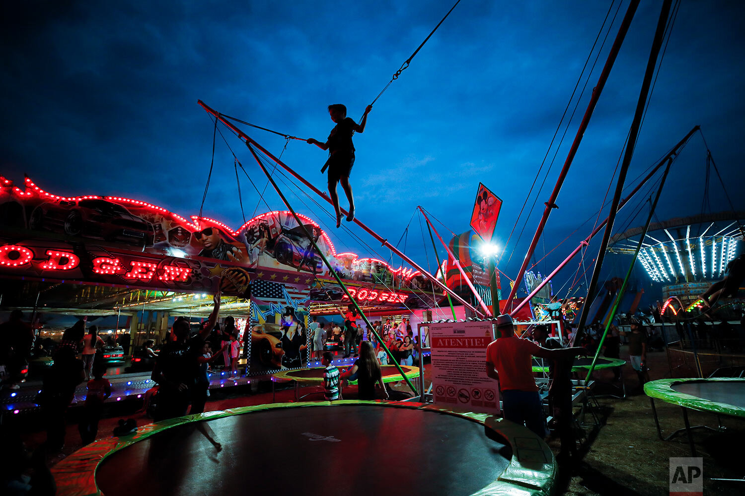 A child jumps on a trampoline at an autumn fair in Titu, southern Romania, Sept. 14, 2019. (AP Photo/Vadim Ghirda)