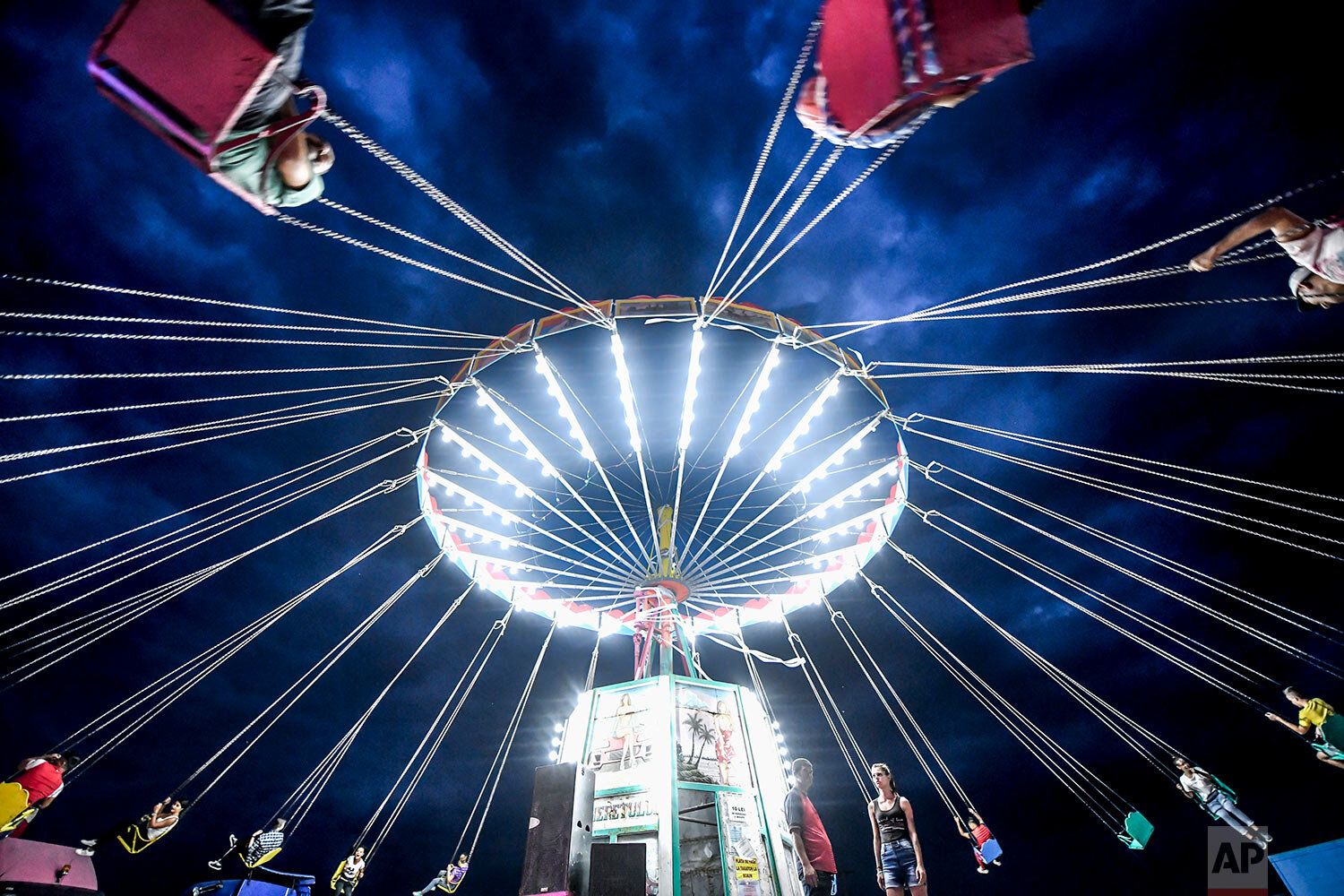 People enjoy a swing ride at an autumn fair in Titu, southern Romania, Sept. 14, 2019. (AP Photo/Andreea Alexandru)