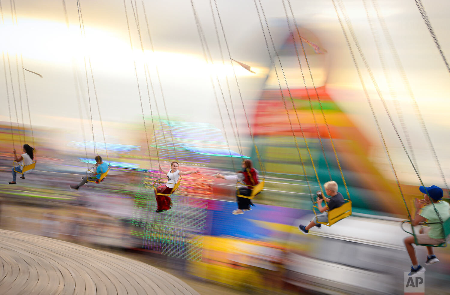 Shot with a slow shutter speed, people enjoy a swing ride at an autumn fair in Titu, southern Romania, Sept. 14, 2019. (AP Photo/Andreea Alexandru)