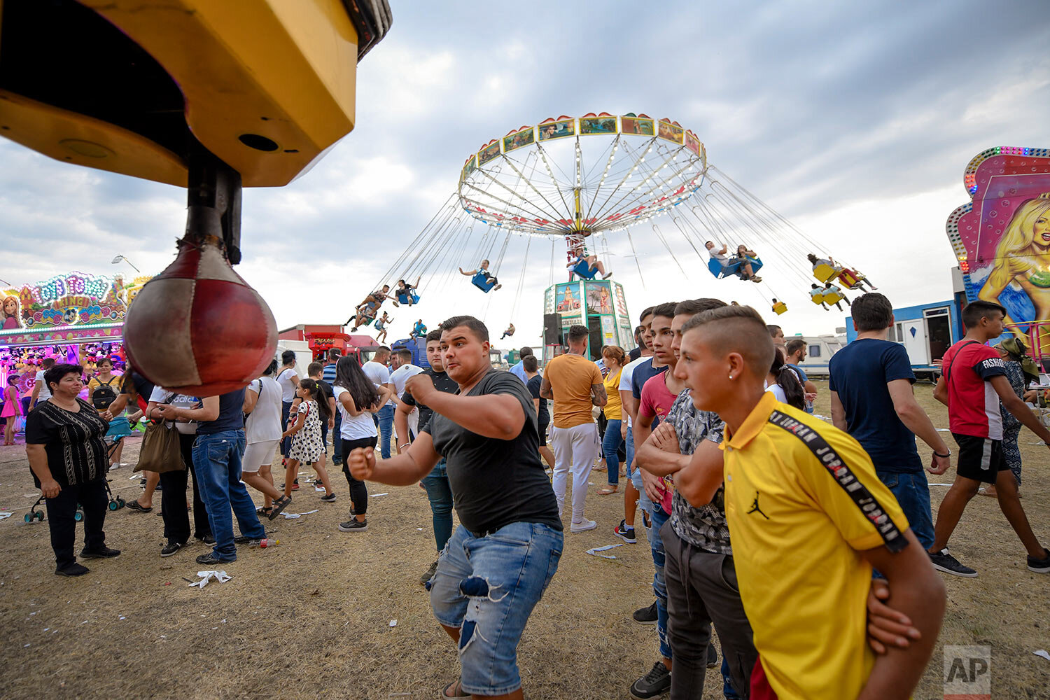 A man tests his strength at a boxing power punch machine at an autumn fair in Titu, southern Romania, Sept. 14, 2019. (AP Photo/Andreea Alexandru)