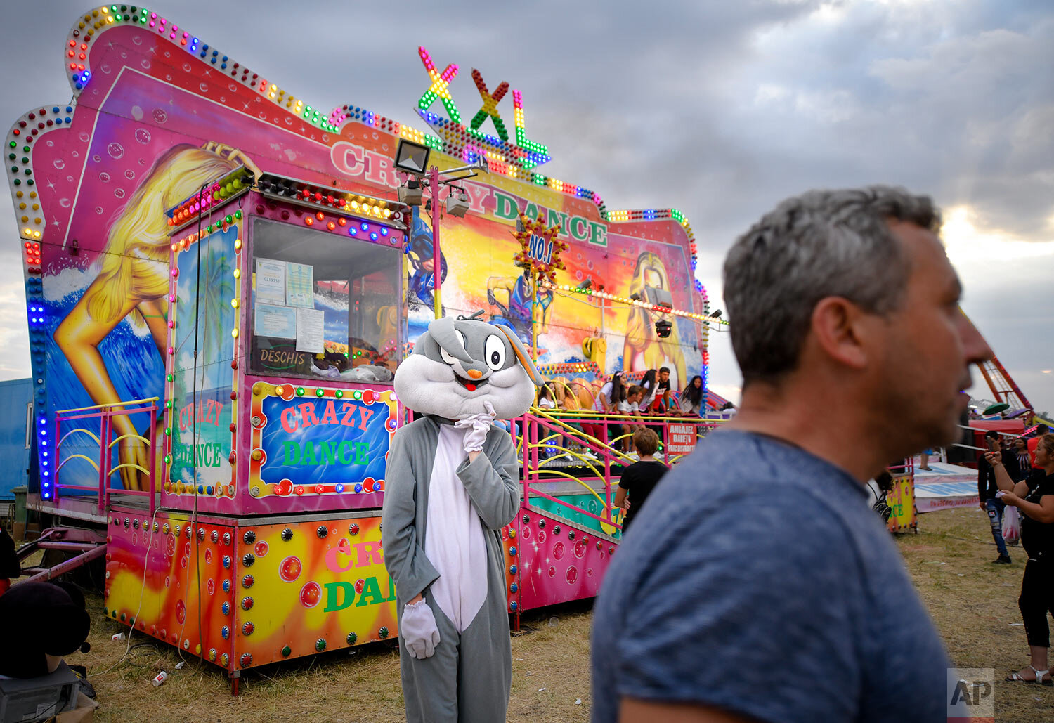 A person wearing a rabbit outfit stands by a ride at an autumn fair in Titu, southern Romania, Sept. 14, 2019. (AP Photo/Andreea Alexandru)