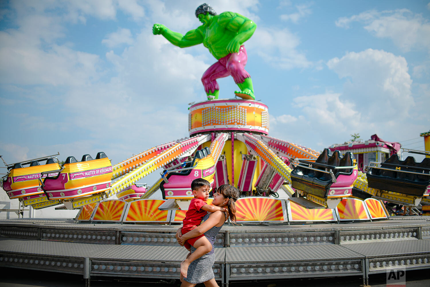 A girl carries a little boy by a merry go round at a fair in Calarasi, southern Romania, Sept. 7, 2019. (AP Photo/Andreea Alexandru)