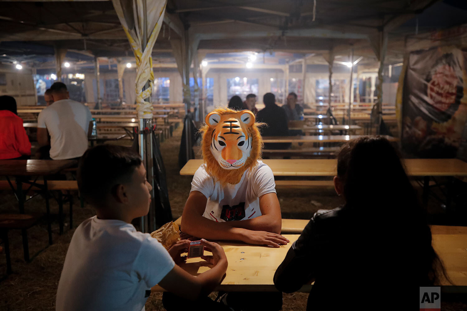 Children, one wearing a tiger mask, sit at a table in the food area of an autumn fair in Titu, southern Romania, Sept. 12, 2019. (AP Photo/Vadim Ghirda)