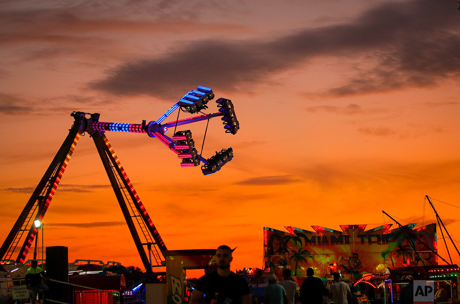 Rides are backdropped by the sunset sky at an autumn fair in Titu, southern Romania, Sept. 12, 2019. (AP Photo/Vadim Ghirda)