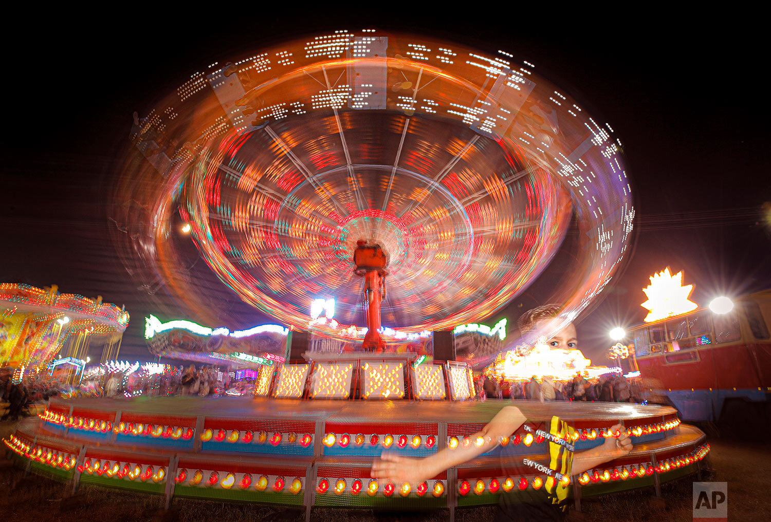 A child runs by a merry go round at an autumn fair in Rosiorii de Vede, southern Romania, Sept. 7, 2019. (AP Photo/Vadim Ghirda)