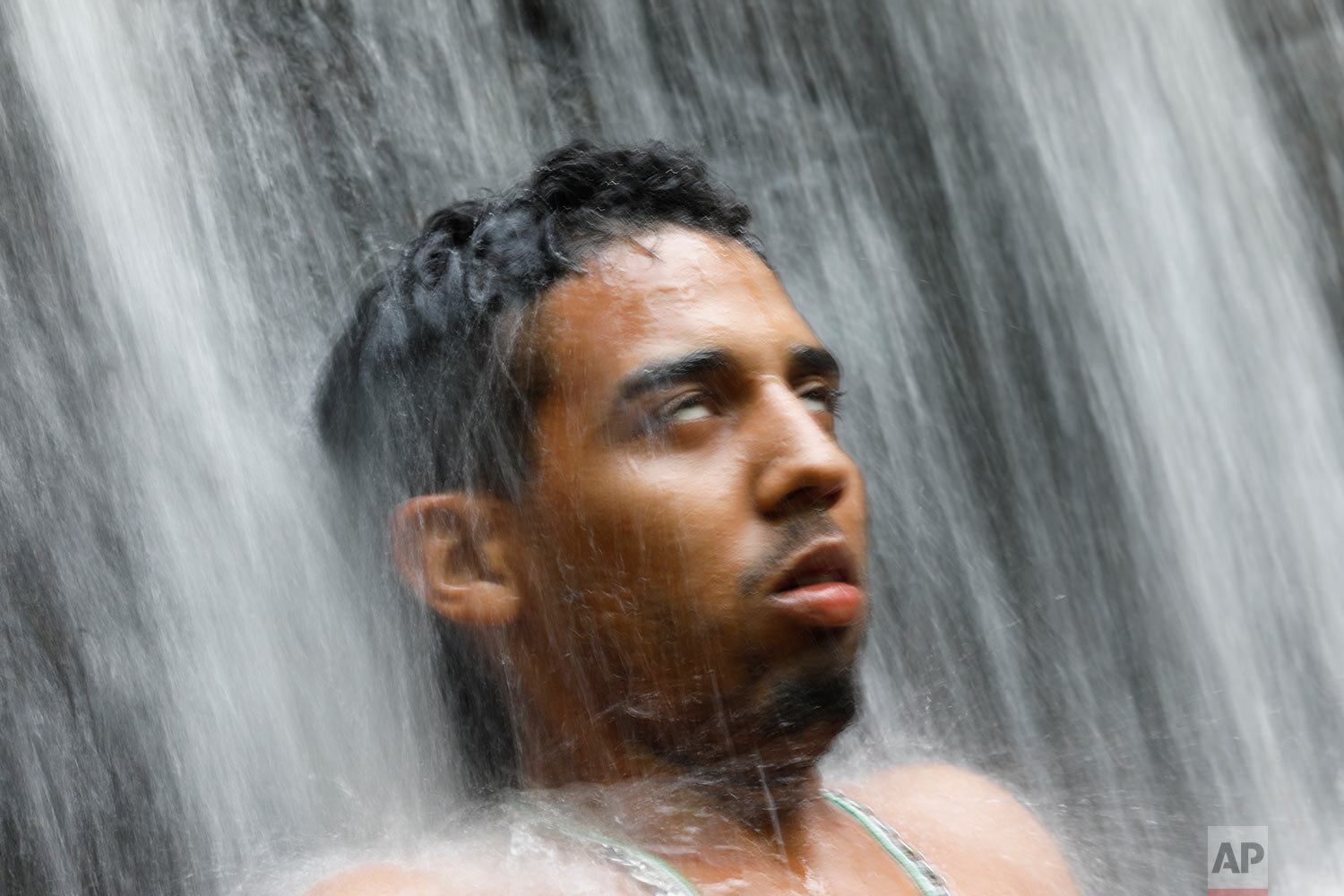 In this photo taken Oct. 12, 2019, a man with his eyes rolled back stands under a waterfall during a spiritual ceremony on Sorte Mountain where followers of indigenous goddess Maria Lionza gather annually in Venezuela's Yaracuy state. (AP Photo/Ariana Cubillos)