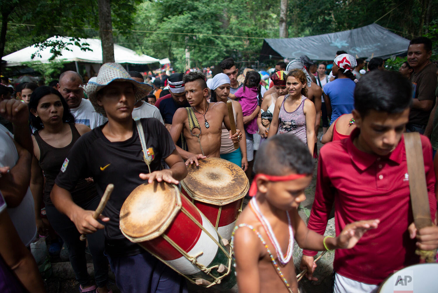 In this photo taken Oct 12, 2019, people play drums during a procession on Sorte Mountain where followers of indigenous goddess Maria Lionza gather annually in Venezuela's Yaracuy state. (AP Photo/Ariana Cubillos)