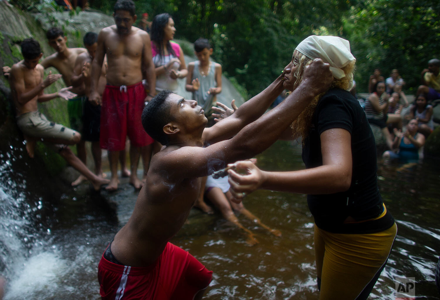 "In this photo taken Oct. 12, 2019, a man's eyes roll backwards as he partakes in a ritual with a spiritual healer known as a ""madrina"" on Sorte Mountain where followers of indigenous goddess Maria Lionza gather annually in Venezuela's Yaracuy state. (AP Photo/Ariana Cubillos)"