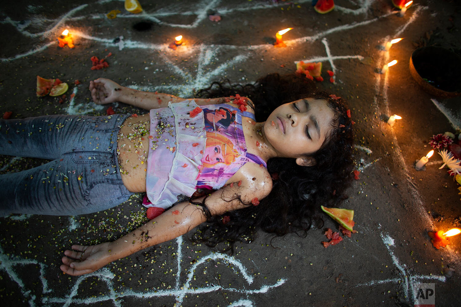 In this photo taken Oct. 13, 2019, girl lies surrounded by candles and designs of white powder during a ceremony on Sorte Mountain where followers of indigenous goddess Maria Lionza gather annually in Venezuela's Yaracuy state. (AP Photo/Ariana Cubillos)