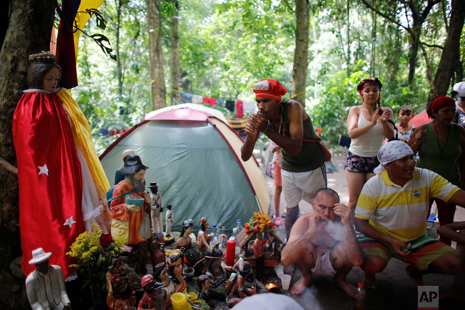 In this photo taken Oct. 12, 2019, followers of indigenous goddess Maria Lionza smoke cigars during purification rituals and to deflect evil spirits, next to an altar featuring her statue, left, on Sorte Mountain where followers of the goddess gather annually in Venezuela's Yaracuy state. (AP Photo/Ariana Cubillos)