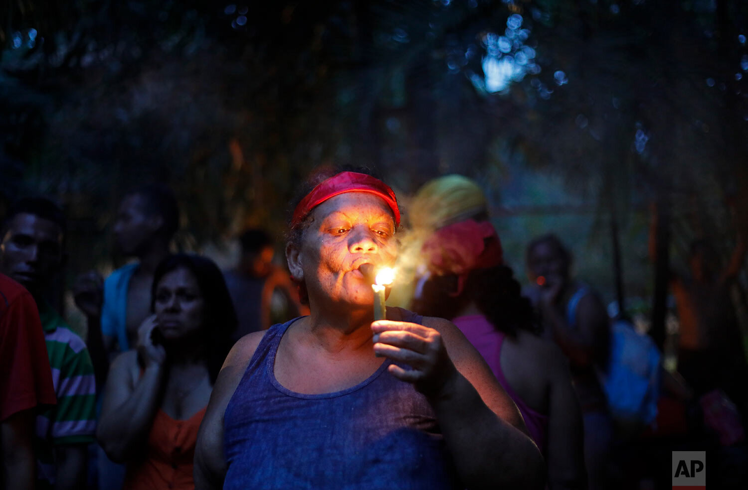In this photo taken Oct. 11, 2019, a woman lights a cigar at the entrance of Sorte mountain to ask for permission to perform spiritual rituals where followers of indigenous goddess Maria Lionza gather annually in Venezuela's Yaracuy state. (AP Photo/Ariana Cubillos)