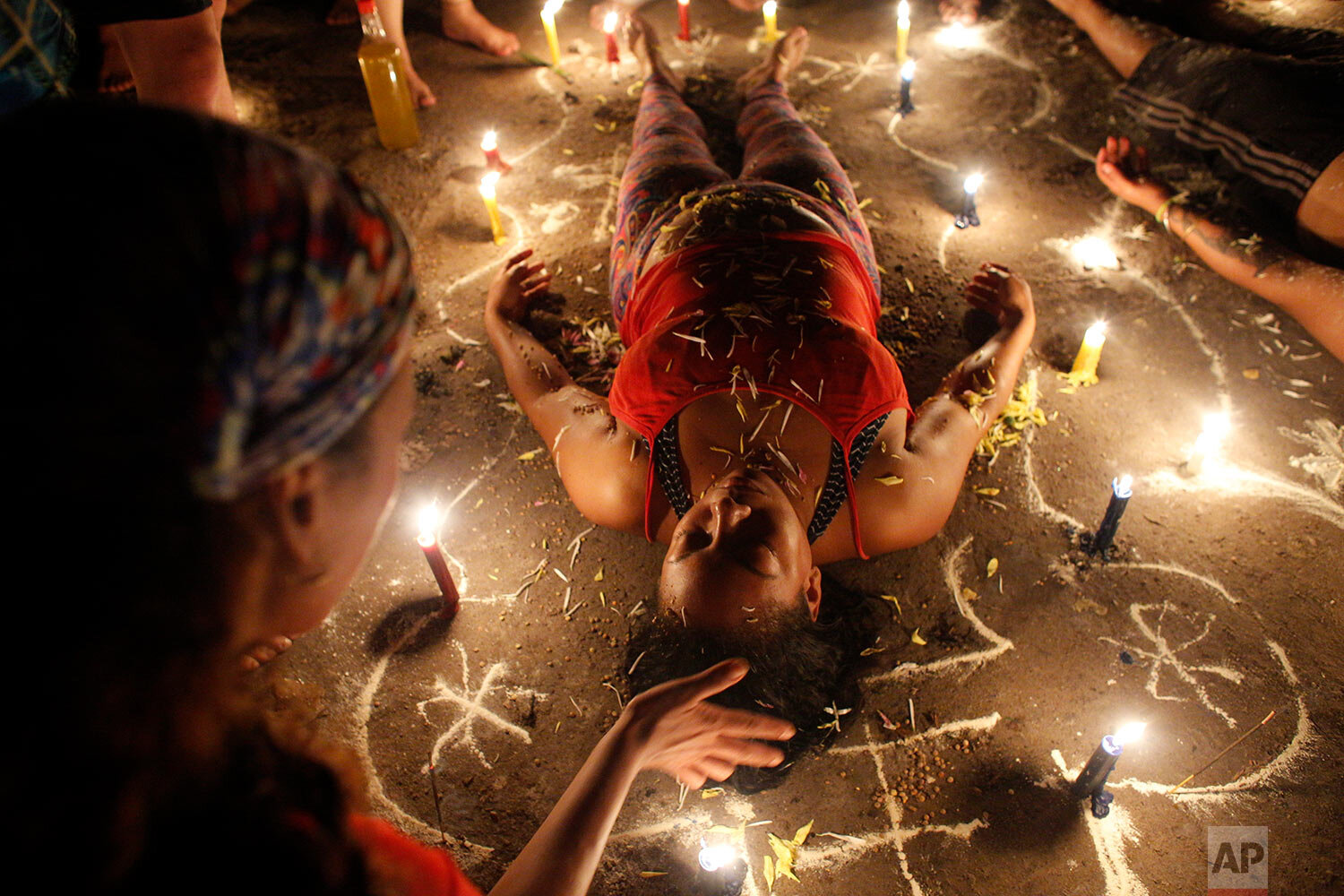 In this photo taken Oct. 11, 2019, a woman surrounded by candles and designs drawn on the ground with white powder lies with her eyes closed during a spiritual ceremony on Sorte Mountain where followers of indigenous goddess Maria Lionza gather annually in Venezuela's Yaracuy state. (AP Photo/Ariana Cubillos)