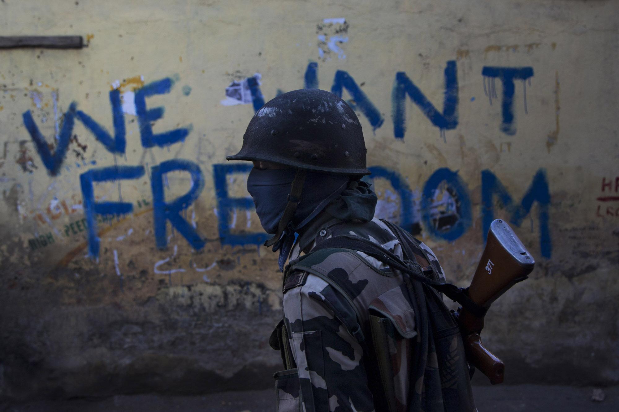 An Indian paramilitary soldier walks past graffiti on a wall in Srinagar, Indian-controlled Kashmir, Aug. 29, 2016.(AP Photo/Dar Yasin)