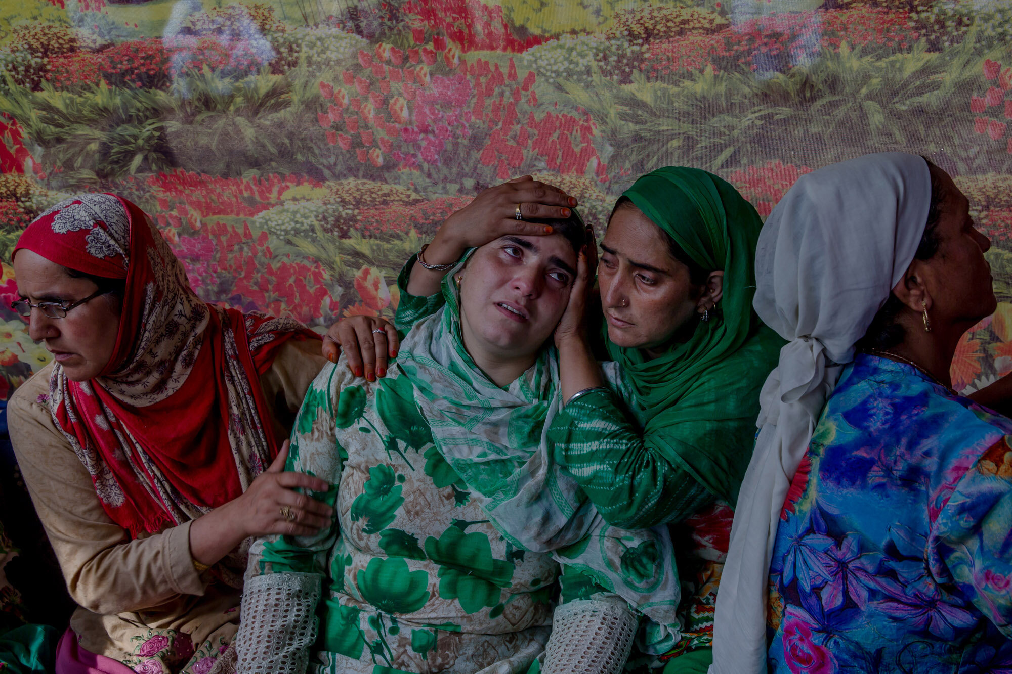 Unidentified relatives comfort the wailing sister of a Kashmiri civilian who was killed during protest near the site of gun battle at her residence in Begumbagh, about 32 kilometers (20miles) south of Srinagar, Indian controlled Kashmir, Aug. 1, 2017. (AP Photo/Dar Yasin)