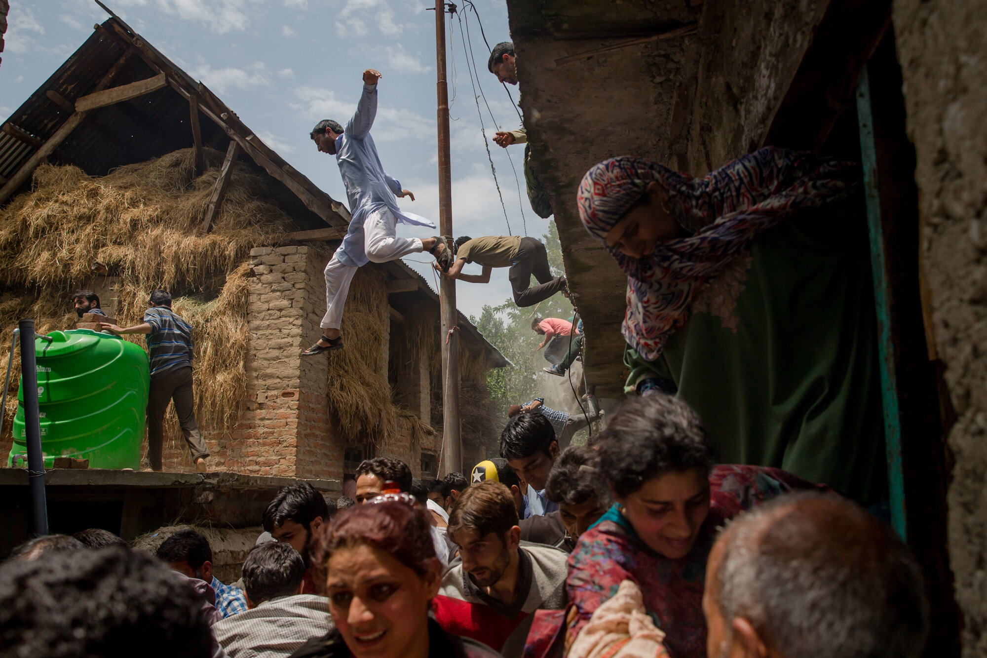 Kashmiri villagers inspecting a home broken in a gun battle flee from it after listening to rumors of Indian military troopers returning again to the positioning, which turned out to be false, in Kundalan village, some 60 kilometers (37 miles) south of Srinagar, Indian managed Kashmir, July, 10, 2018. (AP Photo/Dar Yasin)