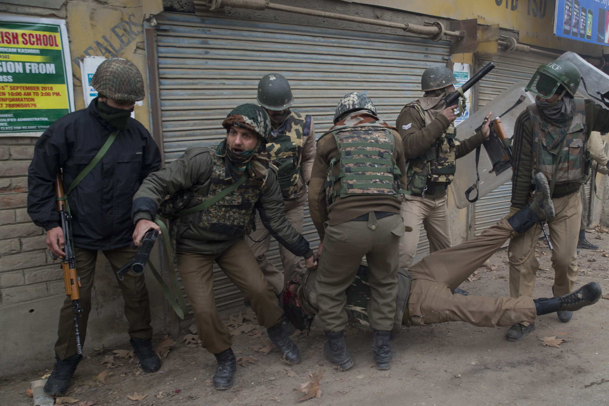 Indian paramilitary soldiers help their wounded colleague as he lies unconscious on the road after he was wounded during a protest near the site of gun battle in Chattergam area of Budgham 25 Kilometers from Srinagar, Indian controlled Kashmir, Nov. 28, 2018. (AP Photo/Dar Yasin)