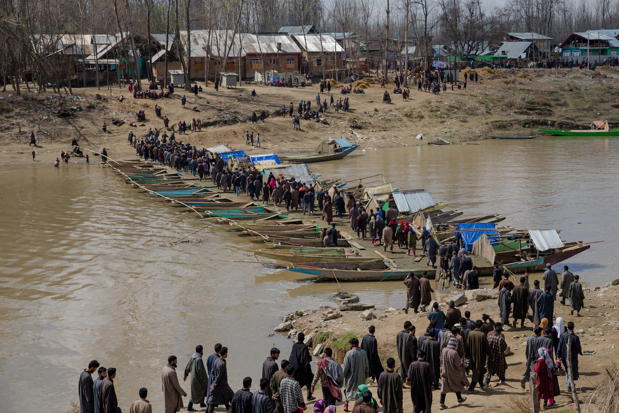 Kashmiri villagers cross a temporary bridge made by lining up boats to make way for people to cross a river to attend funeral of Shabir Ahmad, a suspected rebel in Awantipora, 30 kilometres (18 miles) south of Srinagar, Indian controlled Kashmir, March 16, 2018. (AP Photo/Dar Yasin)