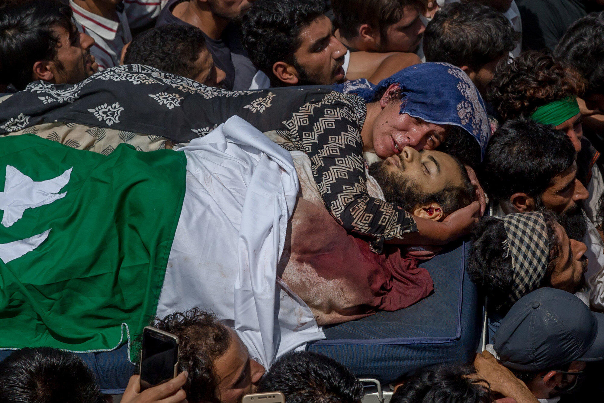 Villagers carry the body of Kashmiri rebel Abid Hamid Mir, as his aunt clings to his body, during his funeral procession in Hajin about 38 Kilometres North of Srinagar, Indian controlled Kashmir, Aug. 5, 2017. (AP Photo/Dar Yasin)